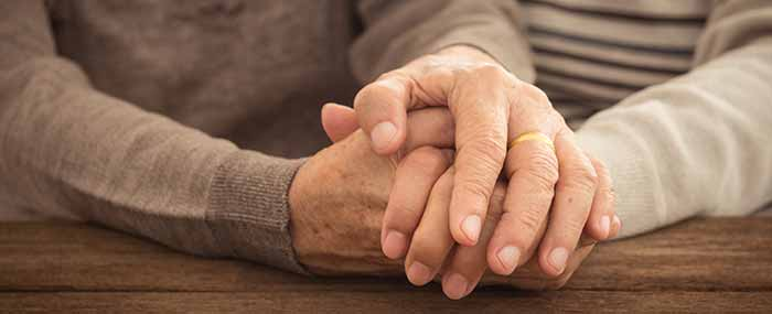 married elderly couple holding hands